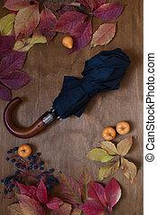 colorful leaves on wooden background black umbrella rain