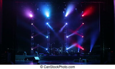 Colorful light flashing and white rays on an empty stage in the dark