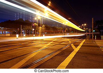 Colorful light rail at night in city