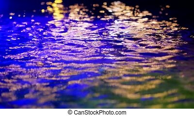 Colorful light reflect on the water at night time.