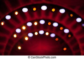 Colorful lights on red background. Defocused.