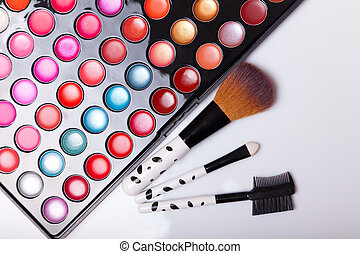 Colorful lip gloss palette with set of brushes, studio shot ...