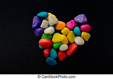 Colorful little pebbles form a heart shape
