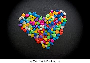 Colorful little pebbles form a heart shape - Colorful little...