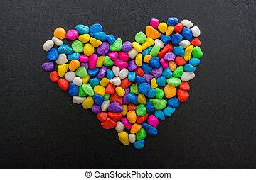 Colorful little pebbles form a heart shape