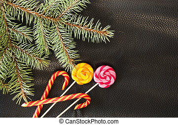 Colorful lollipop and Christmas candy cane on the black color leather background.