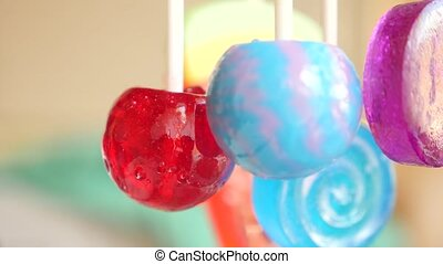 colorful lollipops hang in the air. 4k slow motion.