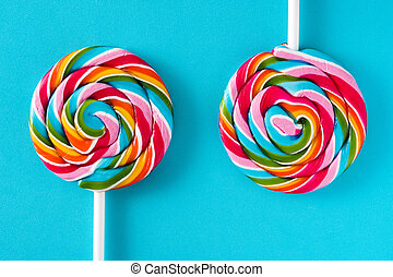 Colorful lollipops on blue background. Top view.