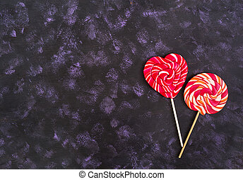 Colorful lollipops on dark background. Top view