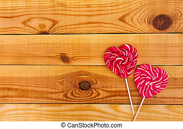 Colorful lollipops on wooden background. Top view