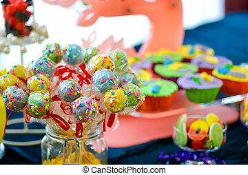 Colorful lollipops placed in a glass jar on a table full of...