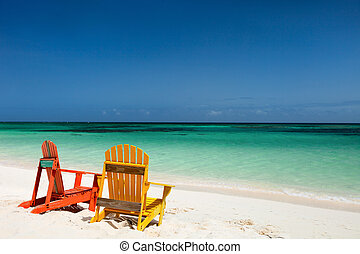 Colorful lounge chairs at Caribbean beach - Colorful yellow...