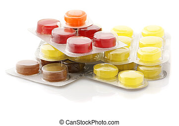 Colorful lozenges in blisters isolated on white background.