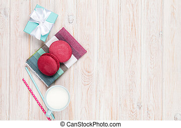 Colorful macarons, cup of milk and gift box on white wooden table with copy space