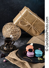 Colorful macarons in a black saucer and a glass of tea on a rustic background with gift boxes
