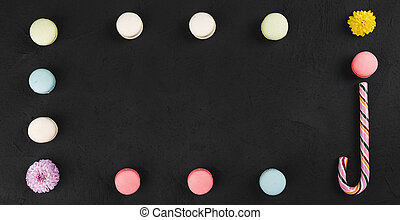 Colorful macarons, lollipop and flowers in the form of a frame on black stone table. Top view with copy space for text