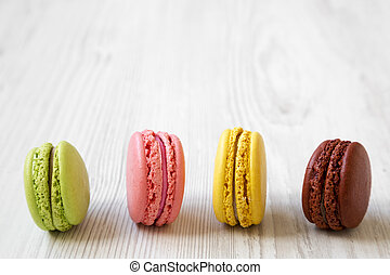 Colorful macarons on a white wooden background, side view. Close-up.