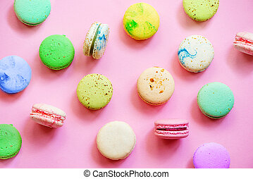 Colorful macarons on pink background