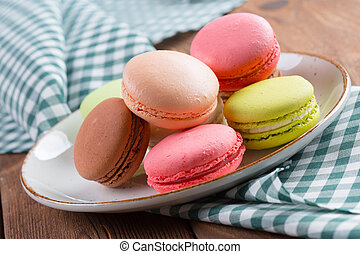 Colorful macaroon cookies on white plate close up