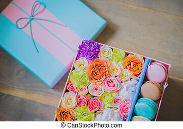 Colorful macaroons and flowers in gift box on table at shop - close up top view