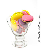 Colorful macaroons in cocktail glass on white background