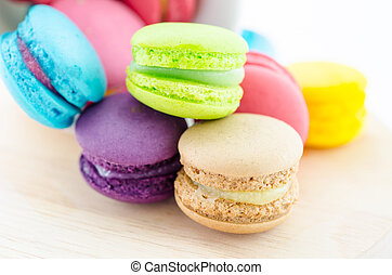 Colorful macaroons in white cup.