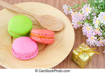 Colorful macaroons in wooden dish and flower.