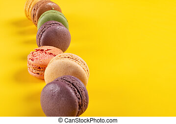 colorful macaroons lined up on a yellow background