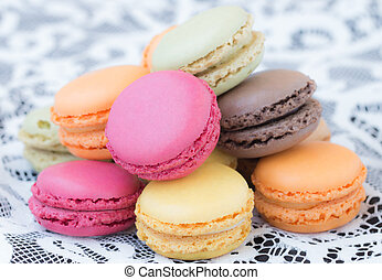 Colorful macaroons on a white lace background.