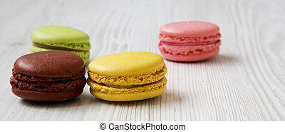 Colorful macaroons on a white wooden background, side view. Close-up.