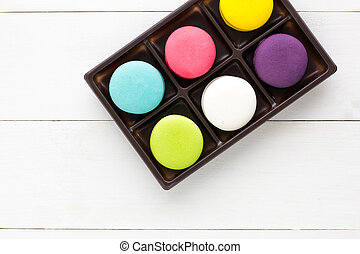 Colorful Macaroons on white wooden background.