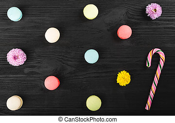 Colorful macaroons on wooden table. Sweet macarons, flowers and lollipop. Top view with copy space for your text