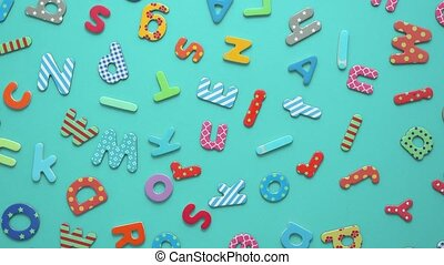 Colorful magnetic, plastic and paper alphabet letters placed...