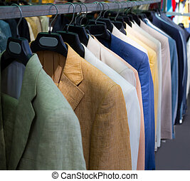 colorful male suits in row in a hanger