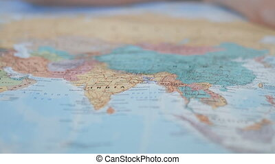 Colorful map of Asia that ends as soon as a hand points at India with a pink pencil