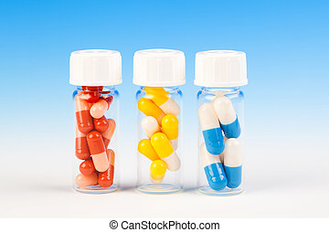 Colorful medical capsules in bottle, on blue background.