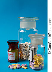 Colorful medical pills in a glass container on a blue background.