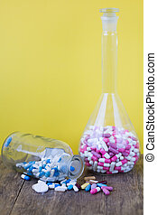 Colorful medical pills in glass containers and in bulk.