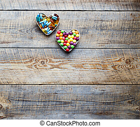 colorful medical pills in shape of hearts on wodden table
