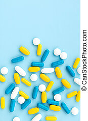Colorful medical pills on blue background. Top view flat lay