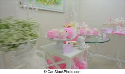 Colorful meringues, delicious cakes on different tables for baby`s celebration