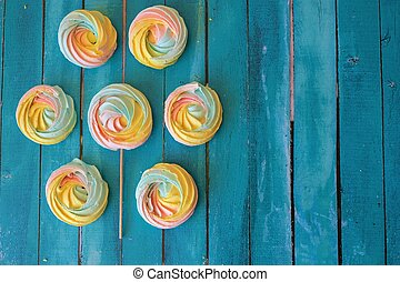 Colorful meringues on wooden background
