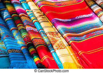 Colorful Mexican serapes hang in row. Mexican rugs from palenque, mexico