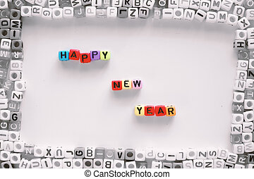 """Colorful of letter beads wording """"HAPPY NEW YEAR"""" in the frame of black and white alphabet cube"""