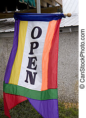 A colorful banner or flag in front of a store saying Ope n