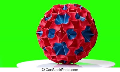 Colorful origami ball on green screen. Blue and red...