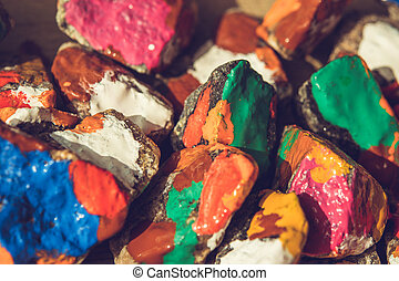 paint spreads on the surface of small stones