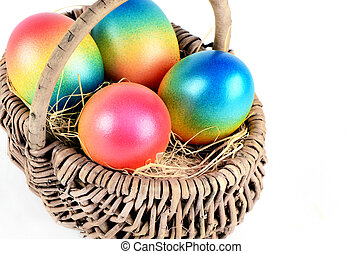 Colorful painted easter eggs in brown basket in white