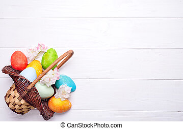 Colorful painted easter eggs in brown basket on a white...