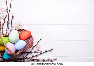 Colorful painted easter eggs in brown basket with branches...
